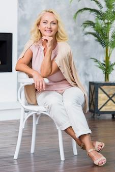 Alte dame des smiley, welche die kamera beim sitzen auf weißem stuhl betrachtet