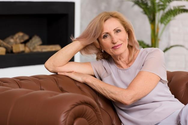 Alte dame, die auf sofa sitzt und kamera betrachtet