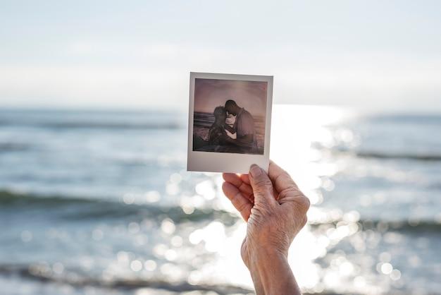 Alte dame, die eine fotografie am strand hält