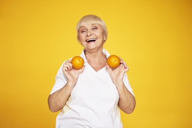 Alte dame in sportkleidung hat spaß mit orangen.