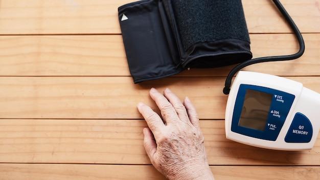 Alte dame wird blutdruck unter verwendung des blutdrucküberwachungskindersatzes überprüft
