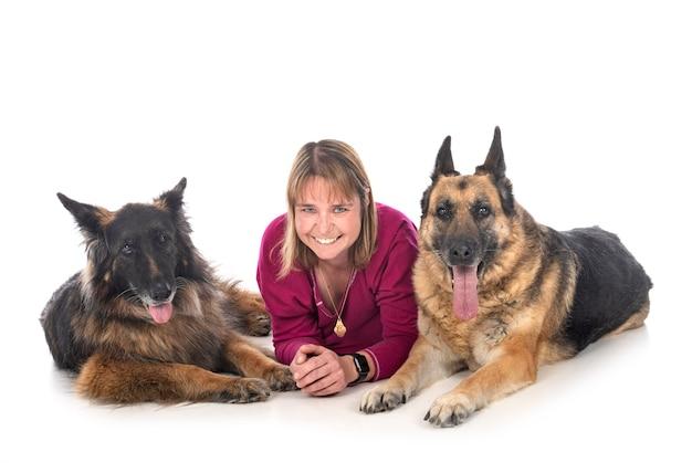 Frauen- und deutsche schäferhunde bleiben am strand