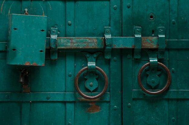 Alte eisentür mit dem verschlussbolzen gemalt mit grüner farbe