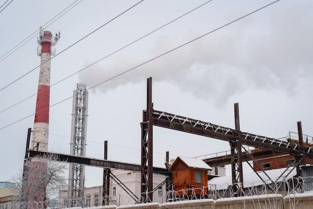 Alte fabrik, rostige strukturen und ein rauchender schornstein. luftverschmutzung. russland
