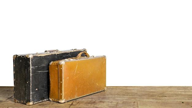 Alte fälle auf holzboden. gepäck- und reisekonzept im retro-stil isoliert auf weißem hintergrund
