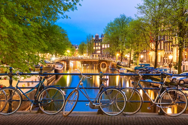 Alte fahrräder auf der brücke in amsterdam, die niederlande gegen einen kanal während des sommerdämmerungssonnenuntergangs.