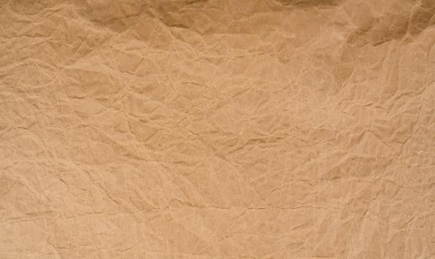 Alte faltige braune papierbeschaffenheit. raue braune kraftpapierstruktur. karton recyceln. rustikales musterdesign. nahaufnahme zerknitterte papiertüte. grunge und zerknittertes pergament.
