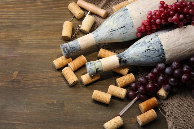 Alte flaschen wein, trauben und korken auf holz