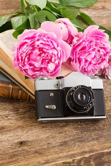 Alte fotokamera mit büchern und frischen pfingstrosenblumen
