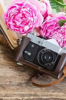 Alte fotokamera mit büchern und pfingstrosenblumen