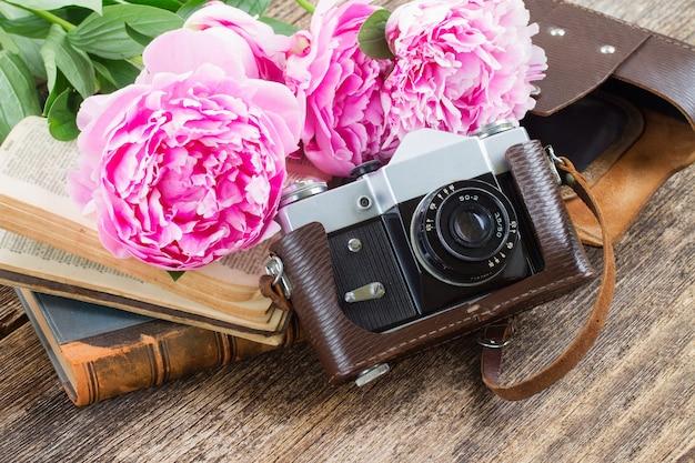Alte fotokamera mit stapel bücher und pfingstrosenblumen