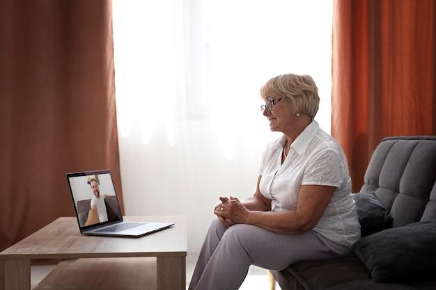 Alte frau bei einem videoanruf mit ihrer familie