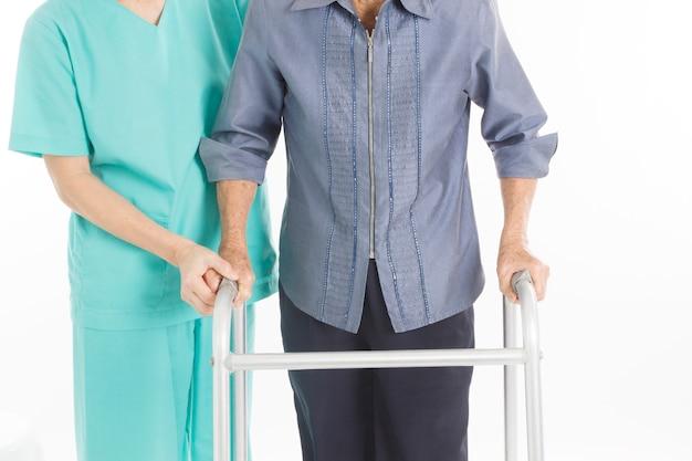 Alte frau bekommt hilfe beim gehen von einer krankenschwester