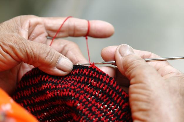 Alte frau der nahaufnahme in der landschaft, thailand, das handgemachte taschen an ihrem haus tuend strickt.