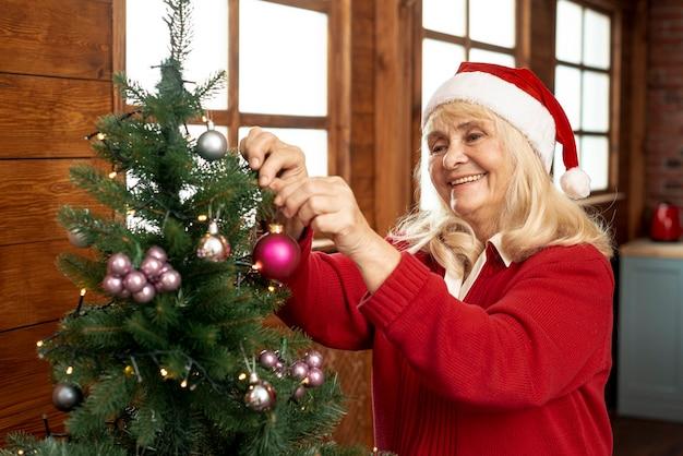 Alte frau des mittleren schusses, die den weihnachtsbaum verziert