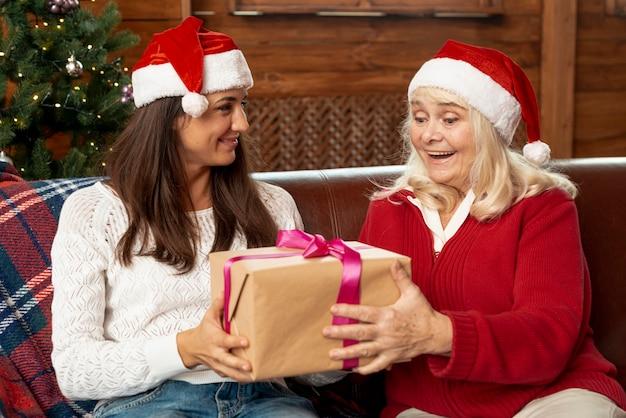 Alte frau des mittleren schusses, die ein geschenk empfängt