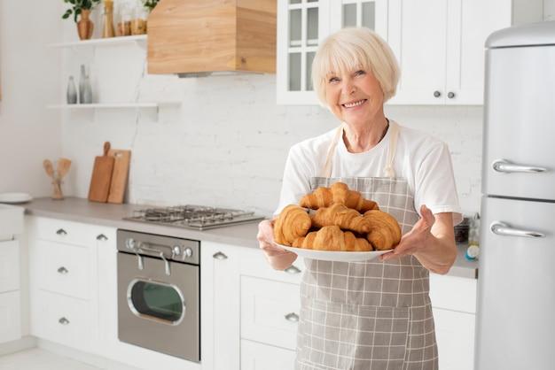 Alte frau des smiley, die eine platte mit hörnchen in der küche hält