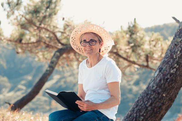 Alte frau, die an einem super sonnigen tag ein buch am strand liest. freiheitskonzept mit kopienraum, entspannung und seniorenruhestandsglück, lächeln in die kamera