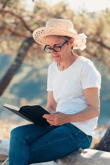 Alte frau, die an einem super sonnigen tag ein buch am strand liest. freiheitskonzept mit kopienraum, entspannung und seniorenruhestandsglück