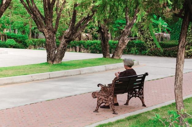 Alte frau, die auf bank am park sitzt