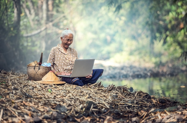 Alte frau, die einen laptop im freien verwendet