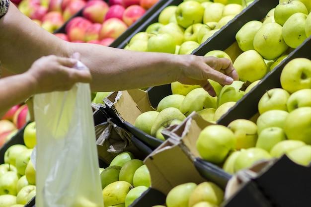Alte frau, die frische äpfel in der lebensmittelabteilung auswählt und in plastiktüte steckt.