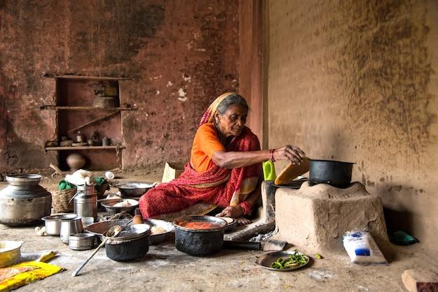 Alte frau, die in einem ländlichen dorf in einer vintage-küche frische lebensmittel backt und kocht?