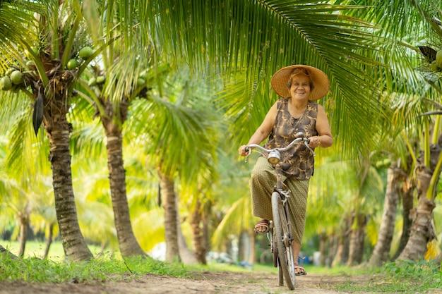 Alte frau, die kokosnuss im kokosnussbauernhof in thailand sammelt.