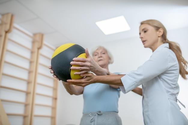Alte frau, die mit einem ball in einem rehabilitationszentrum trainiert