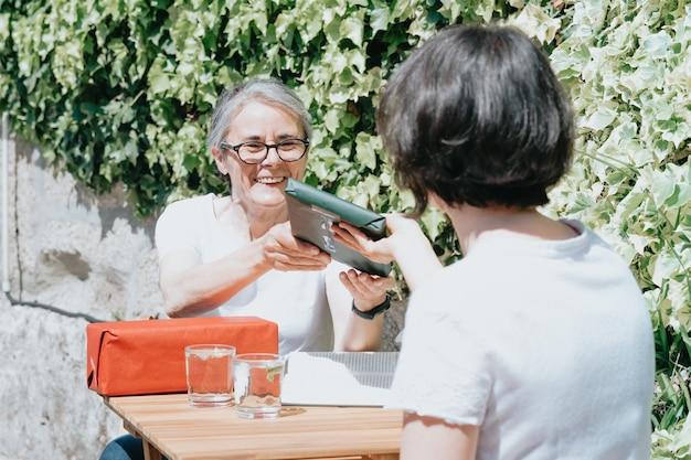 Alte frau, die spaß hat und lächelt, während sie einige geschenke und geschenke von seiner tochter erhält, senior-konzept, sonniger tag