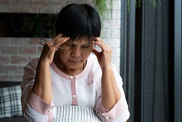 Alte frau, die unter kopfschmerzen, druck, migräne, gesundheitsproblem leidet