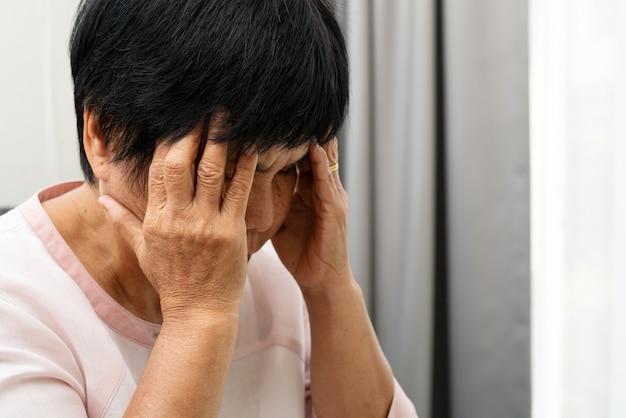 Alte frau, die unter kopfschmerzen leidet