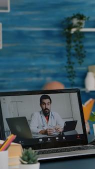 Alte frau, die zu hause am tisch sitzt und einen laptop betrachtet, der fragen zu gesundheitsgesprächen mit dem therapeuten per videokonferenzanwendung beantwortet, hält pillenflasche fernmedizinisches beratungskonzept