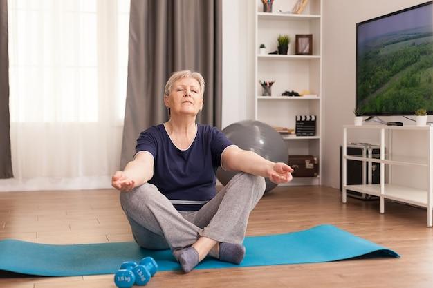 Alte frau, die zu hause auf yogamatte meditiert