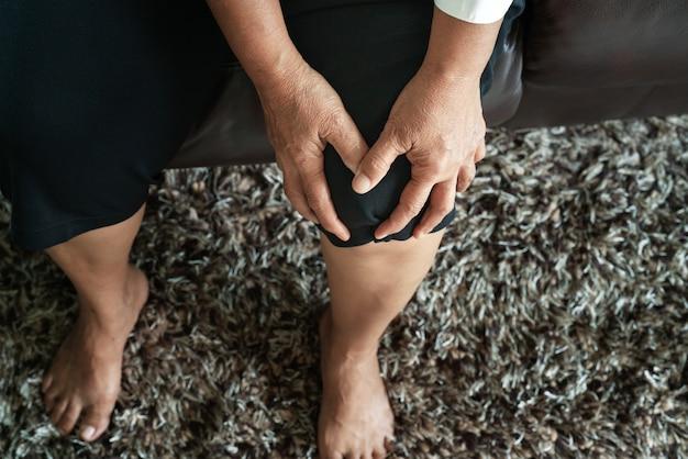 Alte frau, die zu hause unter knieschmerz, gesundheitsproblemkonzept leidet