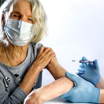 Alte frau erhält den covid-19-impfstoff von einem arzt.