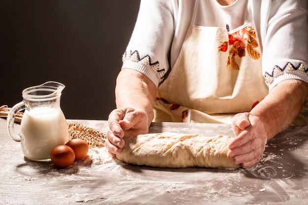 Alte frau, großmutter hände weben brotteig. israelisches authentisches essen. pulver mischen, um leckeres brot zu machen. rohes challa-brot