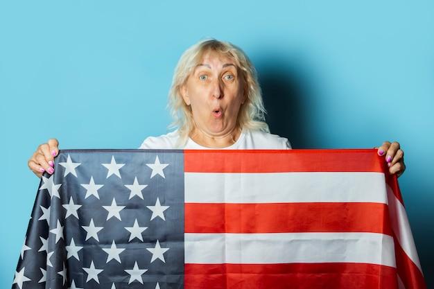 Alte frau hält us-flagge auf einem blauen hintergrund. feierkonzept zum unabhängigkeitstag, gedenktag, auswanderung