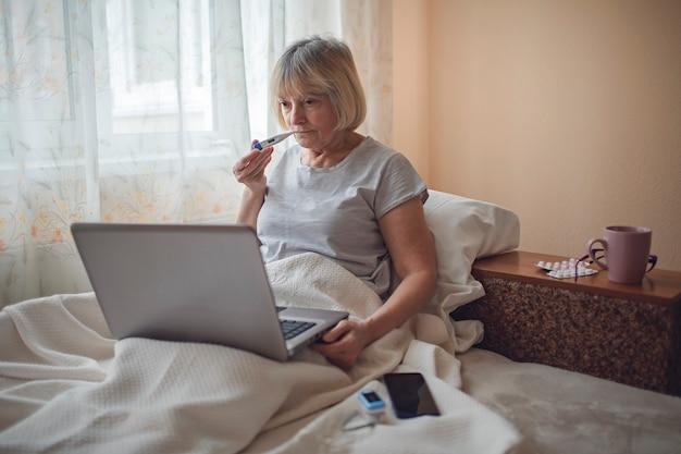 Alte frau im bett, die bildschirm des laptops und beratung mit einem arzt online zu hause, telegesundheit betrachtet