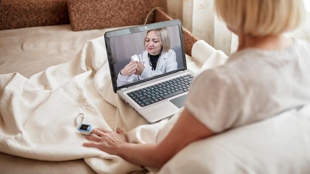 Alte frau im bett, die bildschirm des laptops und beratung mit einem arzt online zu hause, telegesundheitsdienste während der sperrung, entfernter videoanruf, moderne technische gesundheitsanwendung betrachtet