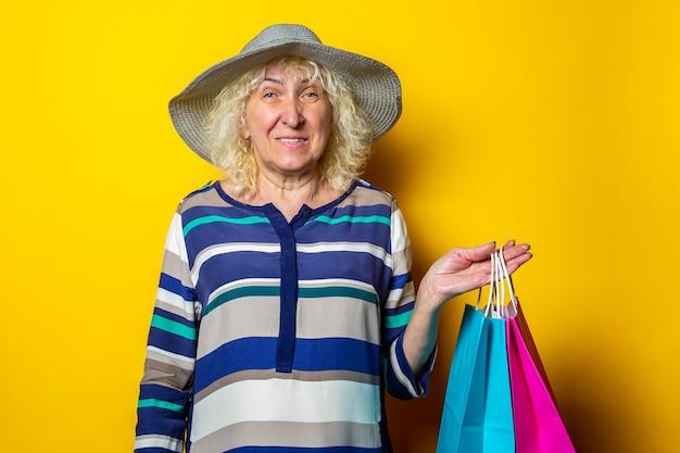 Alte frau im hut, die einkaufstaschen mit einkäufen auf gelbem hintergrund hält.