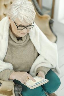 Alte frau in gläsern sitzt zu hause auf dem ledersofa mit einer tablette in ihrer hand