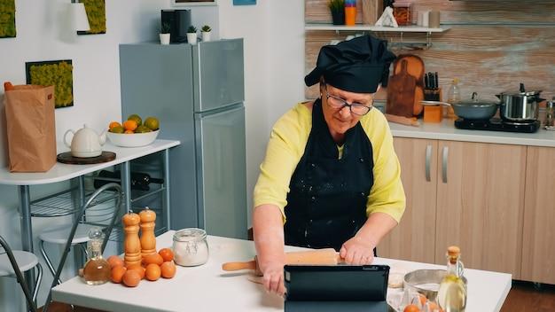 Alte frau mit bone, die an der kulinarischen meisterklasse auf dem laptop teilnimmt. koch im ruhestand, der bäckerratschläge auf dem tablet befolgt, koch-tutorials in sozialen medien lernt und den teig mit nudelholz formt.