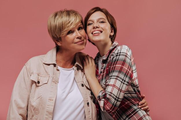 Alte frau mit den kurzen blonden haaren in der kühlen beigen jacke lächelnd und posierend mit brünettem mädchen in karierten kleidern auf rosa hintergrund.