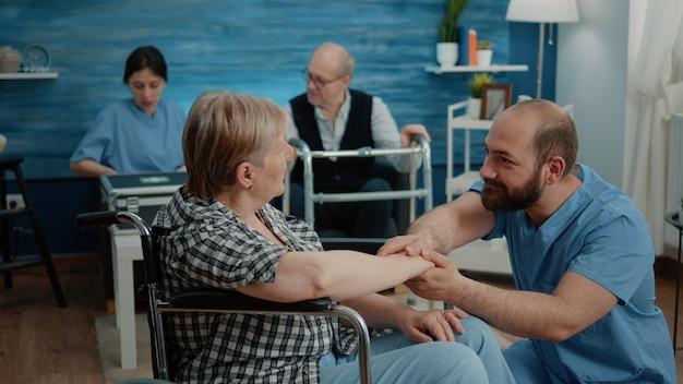 Alte frau mit handicap wird von einer krankenschwester unterstützt