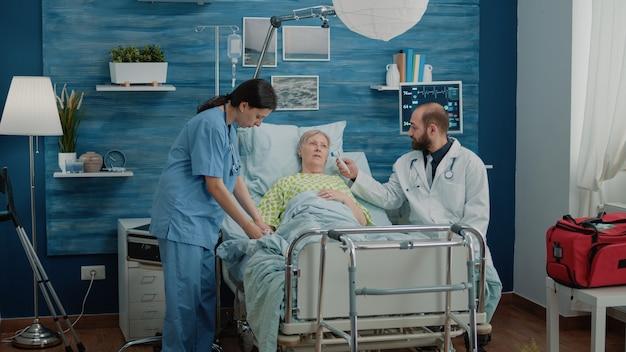 Alte frau mit krankheit, die von einer krankenschwester und einem arzt konsultiert wird