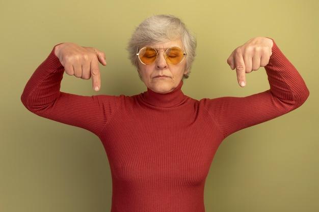 Alte frau mit rotem rollkragenpullover und sonnenbrille, die mit geschlossenen augen nach unten zeigt, isoliert auf olivgrüner wand?