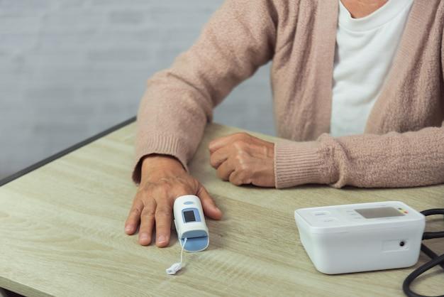 Alte frau mit tonometer, die blutdruckniveau prüft