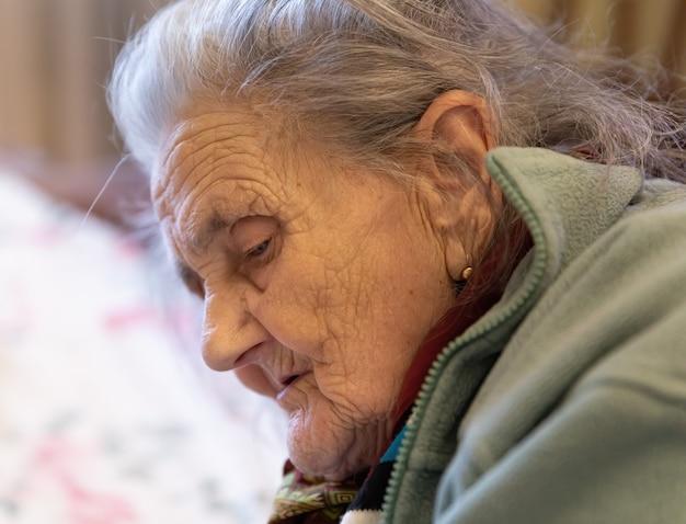Alte frau. porträt der sehr alten müden frau in der depression, die drinnen auf dem bett sitzt