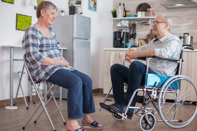 Alte frau und ihr behinderter ehemann im rollstuhl, die in der küche plaudern. ältere person, die ein gespräch mit ehemann in der küche hat. leben mit gehbehinderten menschen